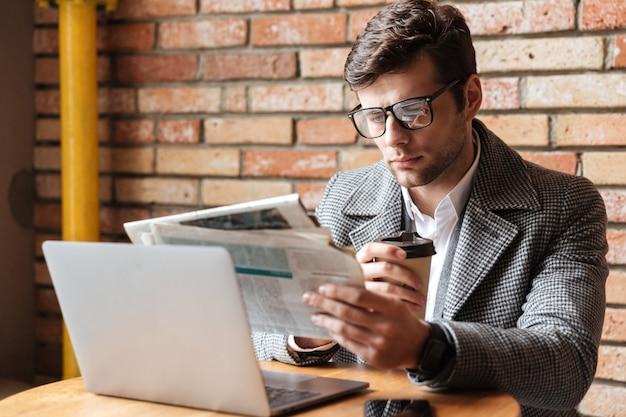 Poważny biznesmen siedzi stołem w eyeglasses