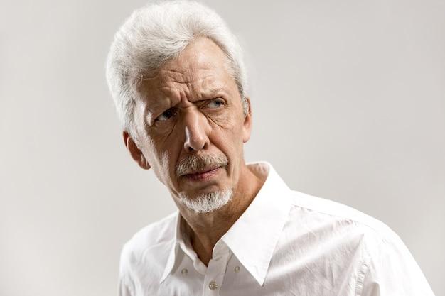 Poważny biznesmen stojący na białym tle na szarej ścianie. portret mężczyzny do połowy długości. ludzkie emocje, koncepcja wyrazu twarzy.