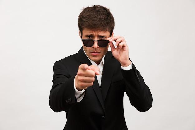 Poważny biznesmen stojący na białym tle nosi okulary przeciwsłoneczne.