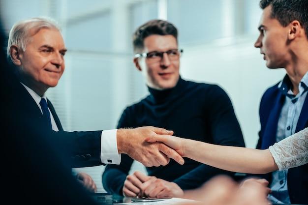 Poważny biznesmen uścisk dłoni z młodym biznesmenem