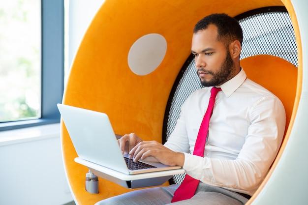Poważny biznesmen używa laptop