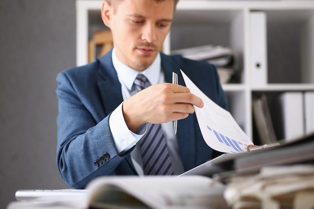 Poważny biznesmen w biurze bada dokumenty