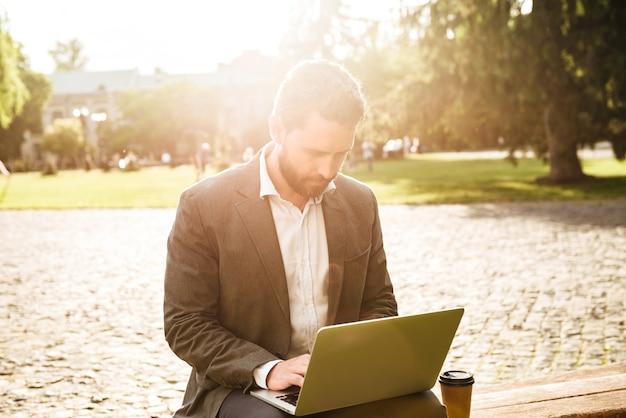 Poważny biznesmen w szarym garniturze klasycznym, siedząc w parku z kawą na wynos i pracując na srebrnym laptopie w słoneczny dzień