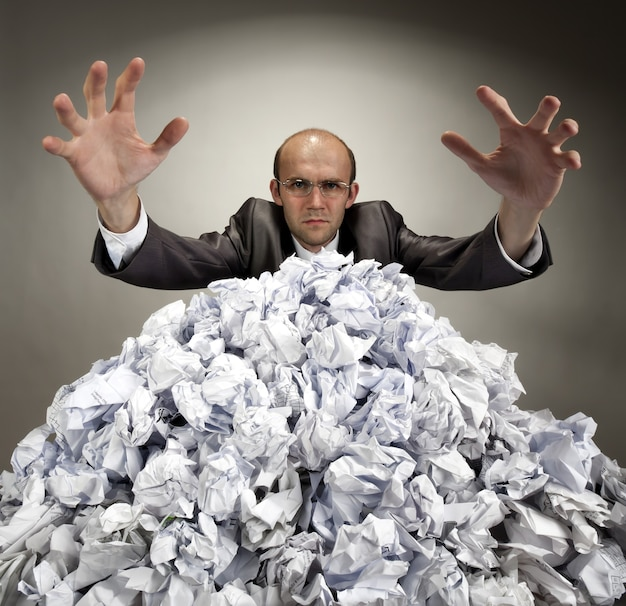 Poważny biznesmen wyciąga rękę z pogniecionych papierów