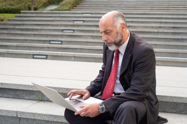 Poważny biznesmen z laptopem na ulicie