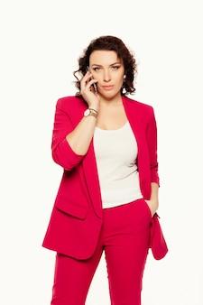 Poważny bizneswoman opowiada na telefonie komórkowym w różowym kostiumu