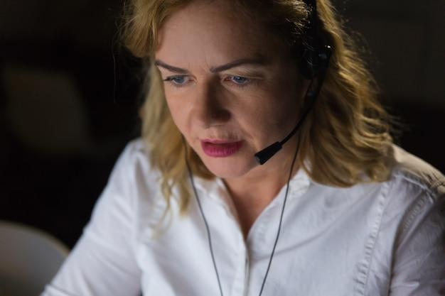 Poważny bizneswoman patrzeje w dół w słuchawki