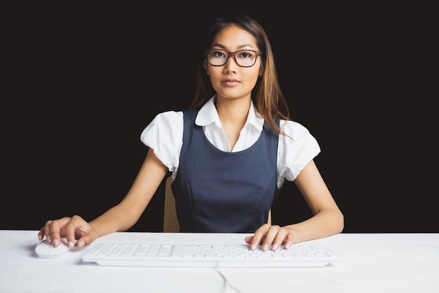 Poważny bizneswoman używa komputer na czarnym tle
