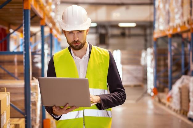 Poważny brodacz patrzy na ciebie podczas pracy jako kierownik logistyki w magazynie