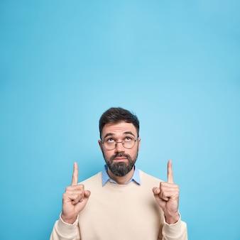Poważny, brodaty brunet, dorosły mężczyzna, skoncentrowany powyżej wskazany z palcami wskazującymi nad głową, pokazuje pustą przestrzeń na kopię