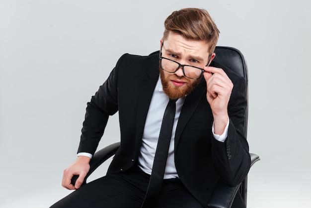 Poważny brodaty człowiek biznesu w okularach, patrząc na kamery i siedząc na fotelu. na białym tle szarym tle