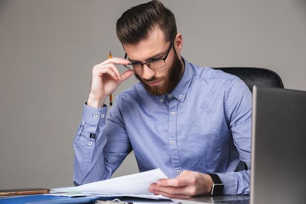 Poważny brodaty elegancki mężczyzna w okularach czytający coś siedząc przy stole w biurze