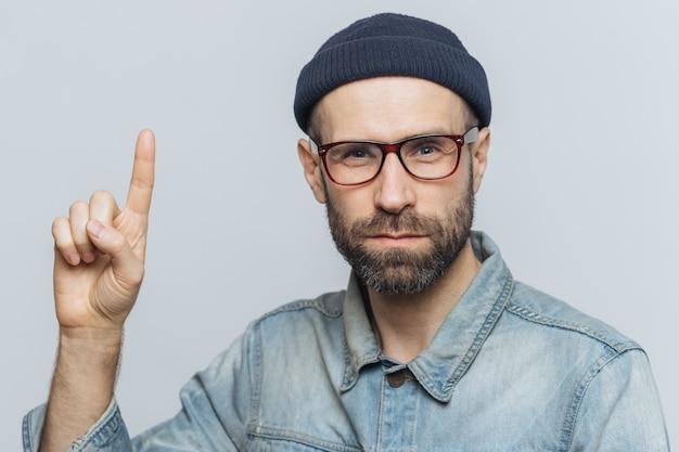 Poważny brodaty mężczyzna nosi okulary, modny kapelusz i dżinsową kurtkę