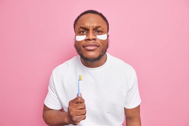 Poważny brodaty mężczyzna o ciemnej karnacji trzyma szczoteczkę do zębów ma zabiegi higieniczne procedura wybielania zębów stosuje plastry upiększające pod oczami