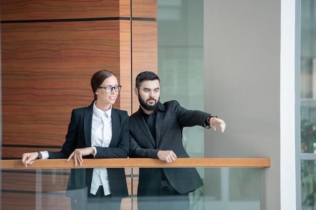 Poważny brodaty mężczyzna stojący z kolegą na balkonie i pokazujący jej nową lokalizację biura