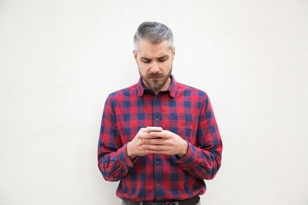 Poważny brodaty mężczyzna używa telefon komórkowego