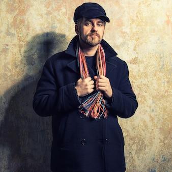 Poważny brodaty mężczyzna w czapce i jesiennym płaszczu, trzymając się za ręce szalika wiszącego na szyi