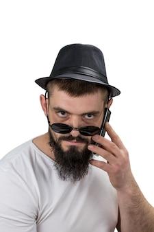 Poważny brodaty mężczyzna w kapeluszu i okularach rozmawia przez telefon na białym tle z miejsca kopiowania.