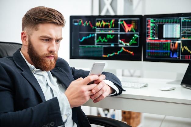 Poważny brodaty młody biznesmen siedzi i używa telefonu komórkowego w biurze