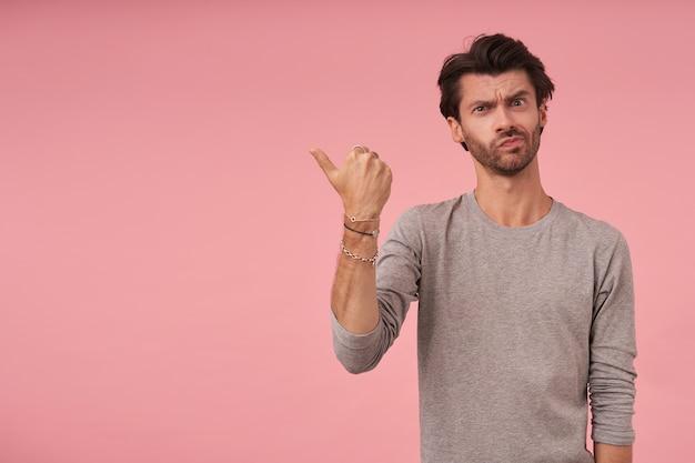 Poważny brodaty młody mężczyzna w szarym swetrze stoi, patrzy i marszczy brwi, wskazując na bok z podniesionym kciukiem