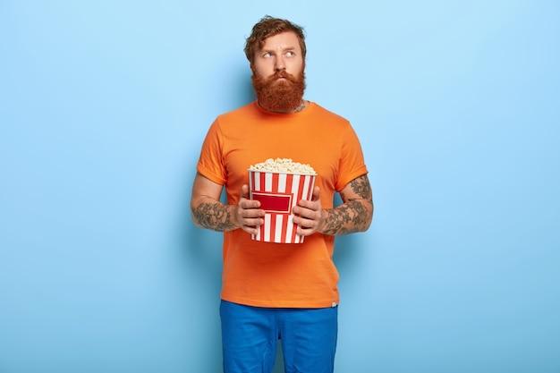 Poważny brodaty rudy mężczyzna pozuje z popcornem