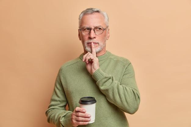 Poważny brodaty siwowłosy mężczyzna pokazuje gest ciszy i prosi o zachowanie tajemnicy na beżowej ścianie
