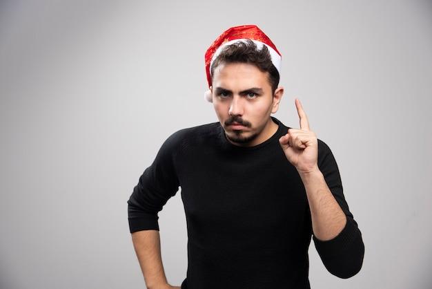 Poważny brunet w czapce świętego mikołaja pokazuje palec i pozuje