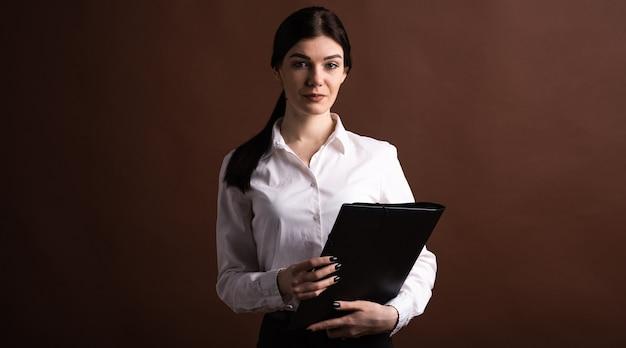 Poważny brunetka bizneswoman z falcówką w rękach