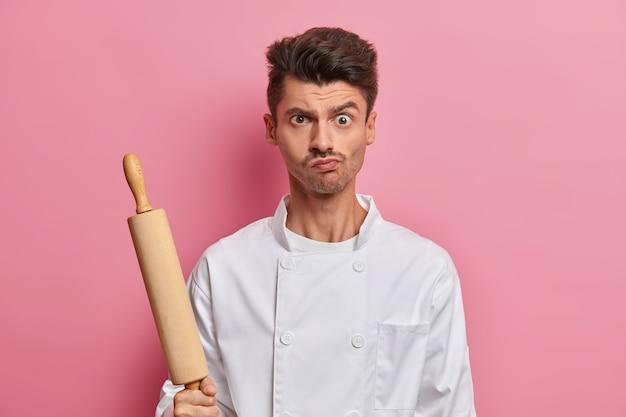 Poważny, brutalny szef kuchni w białym mundurze trzyma drewniany wałek do ciasta