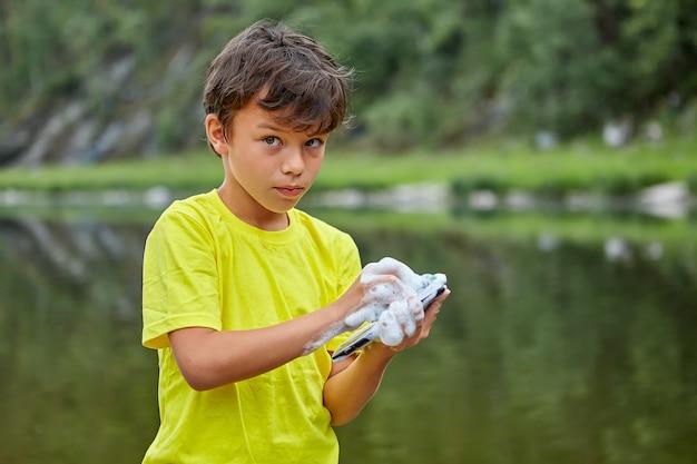 Poważny chłopiec myje telefon komórkowy mydłem, stojąc na brzegu rzeki.