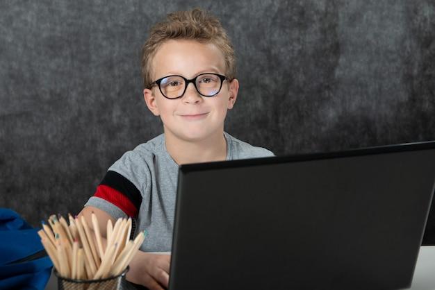 Poważny chłopiec obsiadanie z laptopem