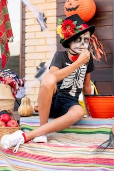 Poważny chłopiec w eleganckim kostiumie na halloween siedzi na dywanie między koszami przed kamerą i ma słodycze przed drzwiami wiejskiego domu