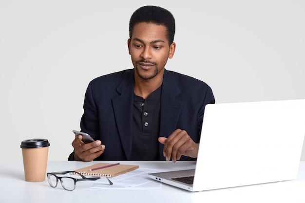 Poważny ciemnoskóry przedsiębiorca w strojach, trzyma telefon komórkowy, czyta wiadomości biznesowe w internecie, pracuje na własny rachunek, robi notatki w notatniku, pije gorący napój, pozuje na pulpicie.