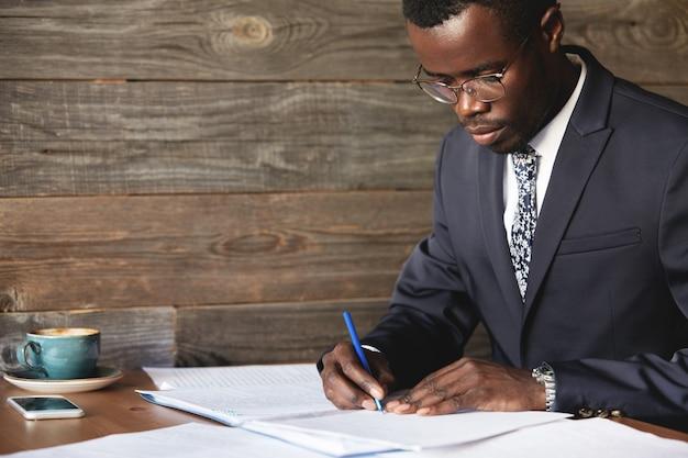 Poważny czarny pracownik korporacji w oficjalnym garniturze i okularach podpisuje lukratywny kontrakt