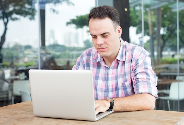 Poważny człowiek pracuje na laptopie w kawiarni na świeżym powietrzu