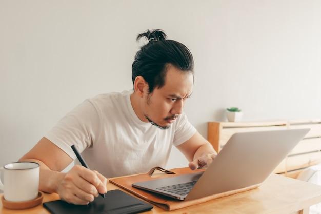 Poważny człowiek pracuje w swoim mieszkaniu