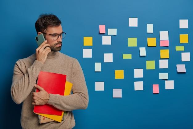 Poważny człowiek rasy kaukaskiej zbiera informacje do pracy projektowej lub pracy w ramach kursu, rozmawia przez telefon komórkowy