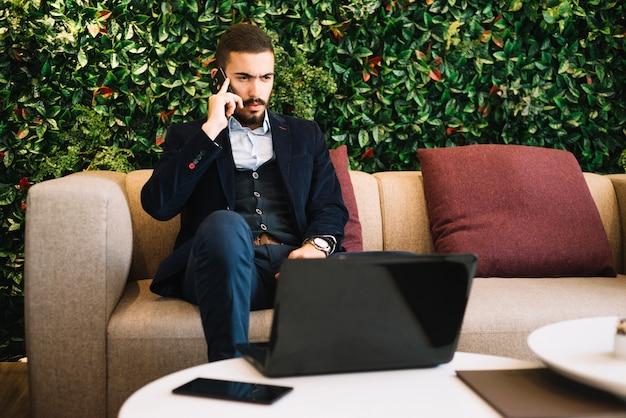 Poważny człowiek rozmawia telefon w kawiarni