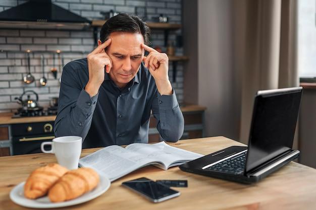 Poważny człowiek siedzi przy stole w kuchni i czyta. patrzy na dziennik i trzyma ręce na głowie. człowiek wygląda na skoncentrowanego.