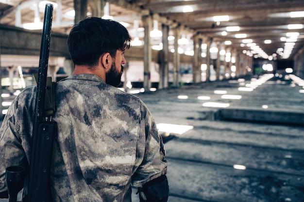 Poważny człowiek stoi w hangarze i trzyma w rękach pistolet do paintballa.