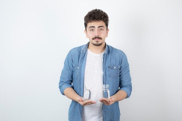 Poważny człowiek trzyma szklankę wody na białym tle.