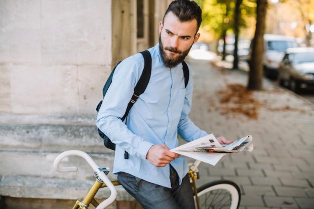 Poważny człowiek z gazety w pobliżu roweru