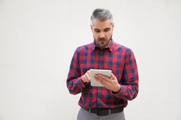 Poważny człowiek za pomocą komputera typu tablet