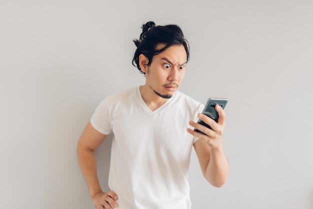 Poważny długowłosy mężczyzna w białej casualowej koszulce używa smartfona.