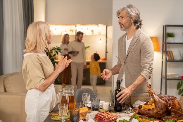 Poważny dojrzały brodaty mężczyzna trzymający butelkę wina, stojąc przy serwowanym stole przed żoną i rozmawiając z nią przed domową imprezą