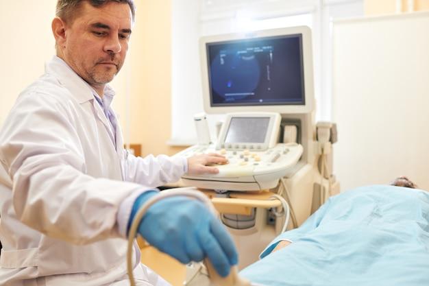 Poważny dojrzały lekarz w fartuchu laboratoryjnym za pomocą sondy podczas wykonywania procedury usg pacjentowi w szpitalu