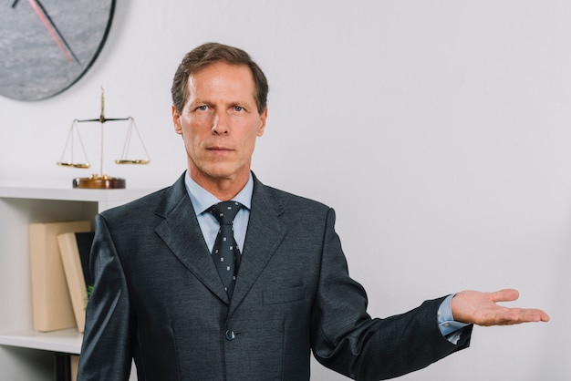 Poważny dojrzały męski prawnik w sala sądowej przedstawiać