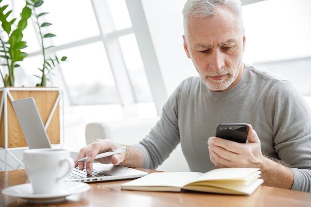 Poważny dojrzały mężczyzna robiący notatki podczas pracy z laptopem i telefonem komórkowym w kawiarni w pomieszczeniu