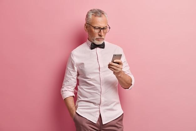 Poważny dojrzały mężczyzna używa smartfona, czyta wiadomości online, trzyma rękę w kieszeni, jest zawsze w kontakcie, odizolowany na różowym tle.