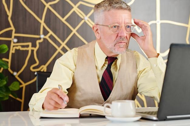 Poważny dojrzały przedsiębiorca poprawiający okulary, czytając szokująco słabe dane z rocznego sprawozdania finansowego